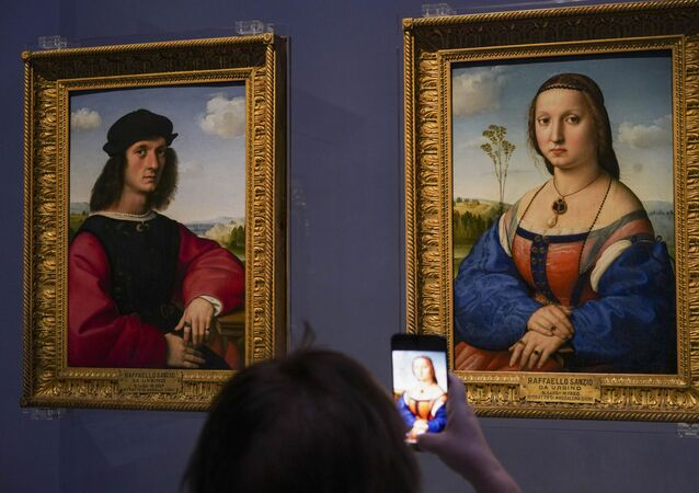 A member of the media takes pictures of 15th century paintings Portraits of Angelo, left, and Maddalena Doni by Raffaello Sanzio da Urbino, during a press tour of the Uffizi museum on the day off its reopening, in Florence, Wednesday, June 3, 2020. The Uffizi museum reopened to the public after over two months of closure due to coronavirus restrictions.