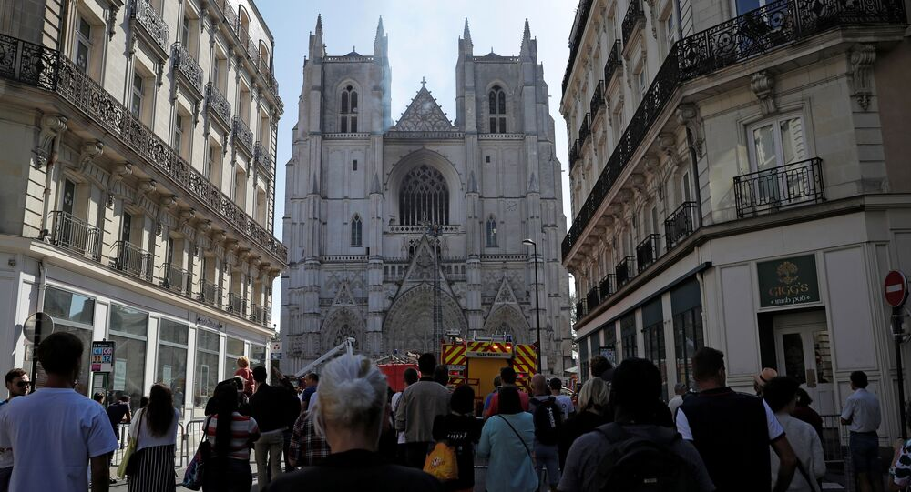 Onlookers gather at the scene of a fire at the Cathedral of Saint Pierre and Saint Paul in Nantes, France, July 18, 2020.