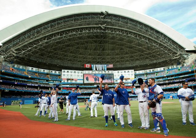 On the last day of the season Toronto Blue Jays players come out of the dugout to tip their hats to fans during the third inning of their American League MLB baseball game against the Tampa Bay Rays in Toronto September 29, 2013.