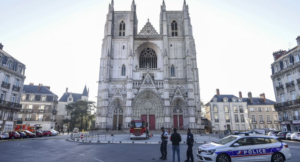 French police officers look at the partially burnt facade of the Saint-Pierre-et-Saint-Paul cathedral in Nantes, western France, on July 19, 2020.