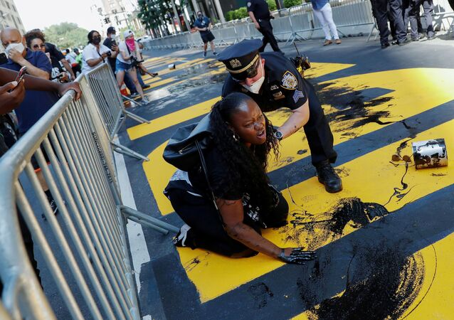 An officer from the New York Police Department (NYPD) attempts to detain a protester smearing paint on the Black Lives Matter mural outside of Trump Tower on Fifth Avenue in Manhattan, New York City, U.S.,18  July 2020.