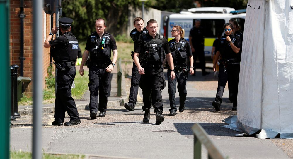 Police officers walk near the block where the suspect of multiple stabbings allegedly lived, in Reading, Britain, 23 June 2020.