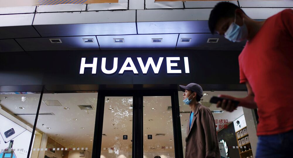 People wearing face masks following the coronavirus disease (COVID-19) outbreak walk past a Huawei store at a shopping mall in Shanghai, China July 14, 2020
