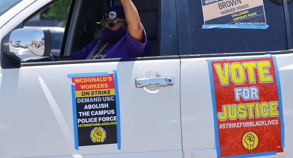 A man gestures as local fast food workers, ride-share drivers, and long-term care workers participate in a caravan protest as part of a nationwide strike for Black lives in Los Angeles, California, U.S., July 20, 2020.