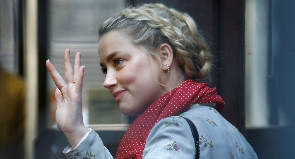 Actress Amber Heard waves as she arrives at the High Court in London on 21 July 2020.
