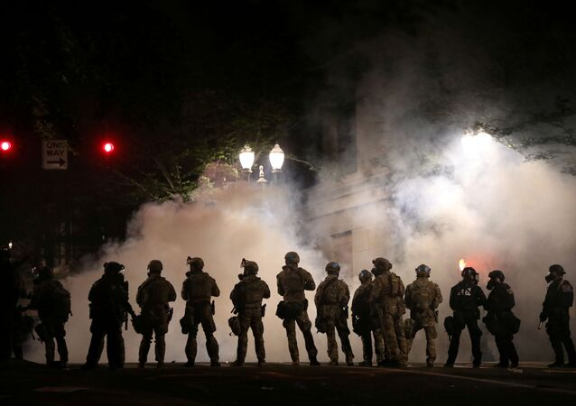 Federal law enforcement officers, deployed under the Trump administration's new executive order to protect federal monuments and buildings, face off with protesters against racial inequality and police violence in Portland, Oregon, U.S., July 21, 2020