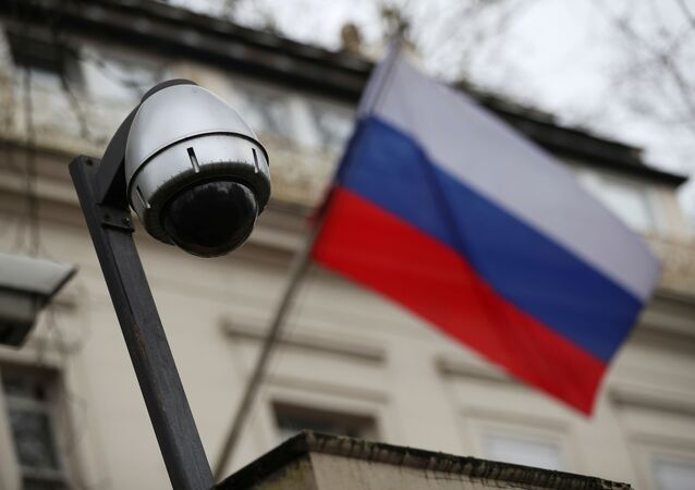 A security camera is seen, and a flag flies outside the consular section of Russia's embassy in London, Britain, March 15, 2018.