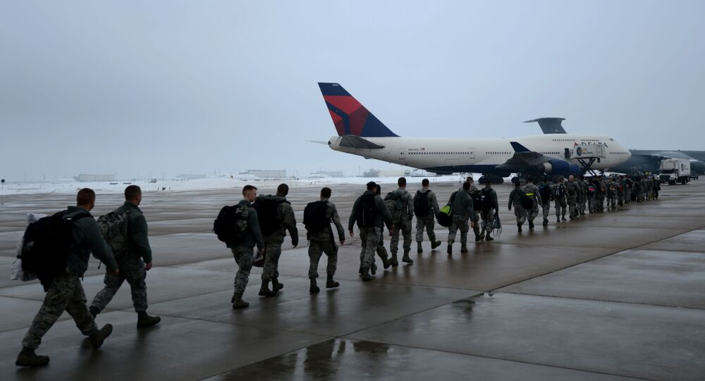 Airmen of the 388th and the 419th Fighter Wings from Hill Air Force Base, Utah prepare to board an aircraft for deployment to Osan Air Force Base, South Korea, Jan. 11, 2014. The 388th and 419th airmen will deploy as part of a Theater Security Package (TSP) to assist with supporting and defending the South Korean border with North Korea. (U.S. Air Force photo by Senior Airman Justyn M. Freeman/Released)