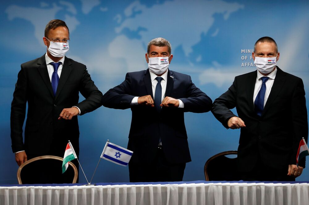 Israeli Foreign Minister Gabi Ashkenazi, his Hungarian counterpart Peter Szijjarto and Israeli Minister of Science and Technology Izhar Shay give elbow bump greetings during their meeting in Jerusalem 20 July 2020.
