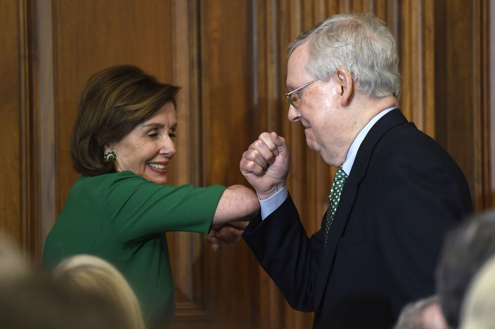 House Speaker Nancy Pelosi of Calif., left, and Senate Majority Leader Mitch McConnell of Ky., right, bump elbows as they attend a lunch with Irish Prime Minister Leo Varadkar on Capitol Hill in Washington, Thursday, 12 March 2020.