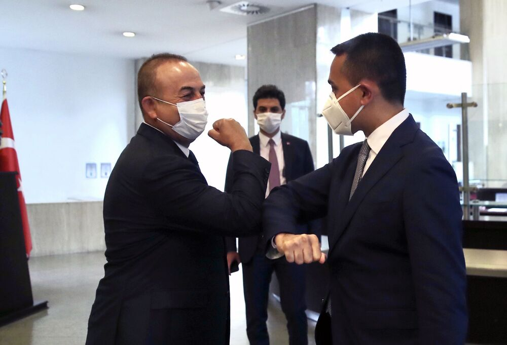 Turkey's Foreign Minister Mevlut Cavusoglu, left, and Italy's Foreign Minister Luigi Di Maio greet each other by using their elbows before their talks, in Ankara, Turkey, Friday, 19 June 2020.