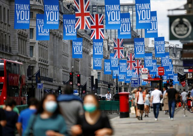 People walk underneath Union Jack flags and banners with a message reading Thank you #ourheroes as restrictions are eased following the outbreak of the coronavirus disease (COVID-19) in Regent Street, London, Britain July 12, 2020
