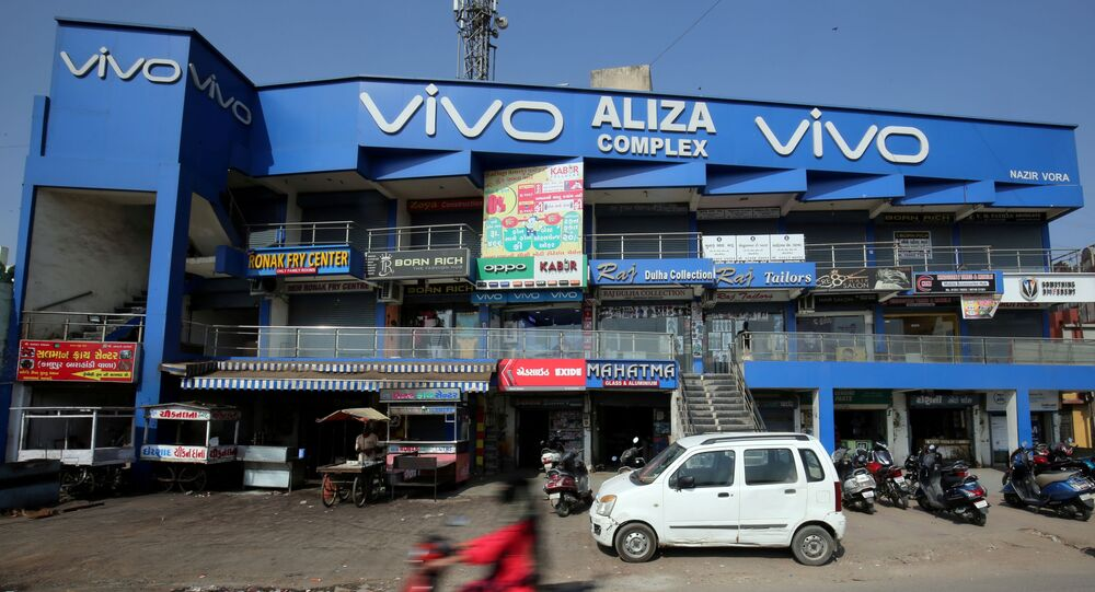 A scooterist rides past a shopping complex with the billboard of Chinese smartphone maker Vivo in Ahmedabad, India, December 14, 2018