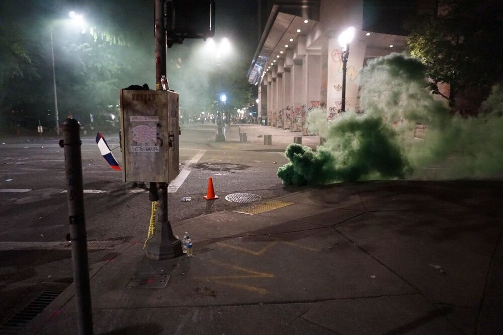 Green fumes are rising as a smoke pellet was launched at the protests