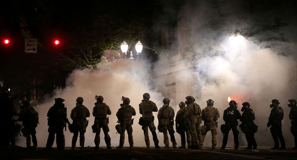 FILE PHOTO: Federal law enforcement officers, deployed under the Trump administration's new executive order to protect federal monuments and buildings, face off with protesters against racial inequality and police violence in Portland, Oregon, U.S., July 21, 2020. REUTERS/Caitlin Ochs/File Photo