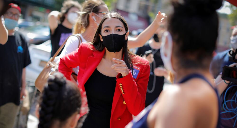U.S. Rep. Alexandria Ocasio-Cortez (D-NY) speaks with local resident Upkar Chana and her daughter Aradhya Vaid while greeting voters during the Democratic congressional primary election in the Queens borough of New York City, New York, U.S., June 23, 2020.