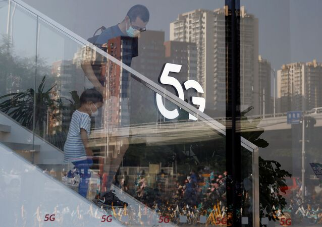 A man and a child wearing face masks following the coronavirus disease (COVID-19) outbreak walk past a 5G sign inside a Huawei store at a shopping mall in Beijing, China July 14, 2020