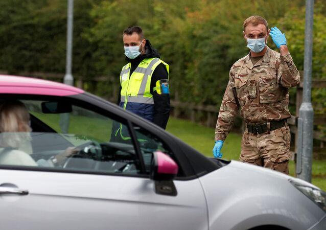 A soldier wearing a protective mask gestures as he directs cars into a coronavirus disease (COVID-19) testing center, as Blackburn with Darwen Council imposes local restrictions in an effort to avoid a local lockdown being forced upon the area, amid the coronavirus disease (COVID-19) outbreak, in Blackburn, Britain July 16, 2020