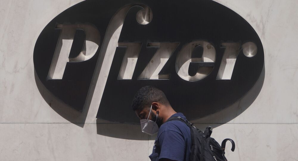 A man walks past a sign outside Pfizer Headquarters in the Manhattan borough of New York City, New York, U.S., July 22, 2020
