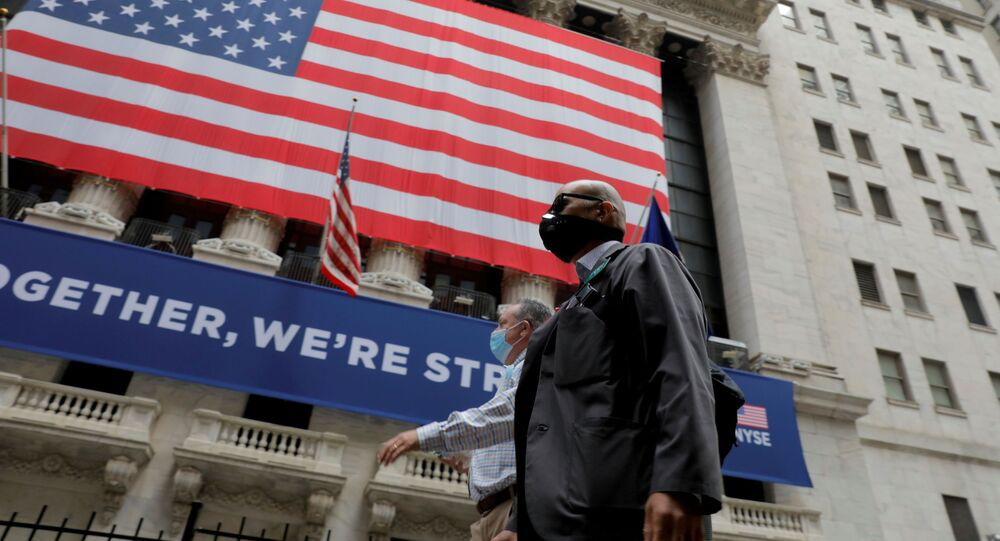 Traders walk past the New York Stock Exchange as the building opens for the first time since March while the outbreak of the coronavirus disease (COVID19) continues in the Manhattan borough of New York, U.S., May 26, 2020.