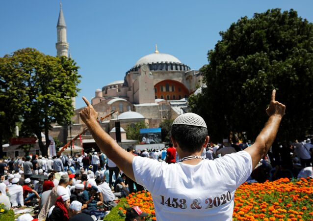 A man gestures as people wait for the beginning of Friday prayers outside Hagia Sophia Grand Mosque, for the first time after it was once again declared a mosque after 86 years, in Istanbul, Turkey, July 24, 2020