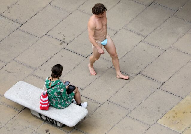 A man wearing a surgical mask as G-string walks past a woman, as the spread of the coronavirus disease (COVID-19) continues, on Oxford Street in London, Britain July 24, 2020