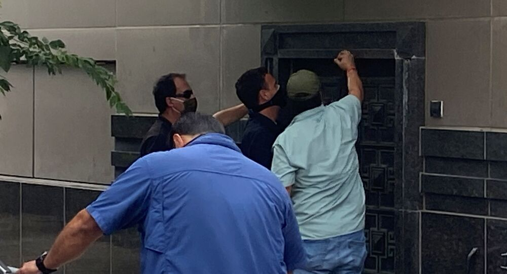 A group of people use power tools to try to pry open a rear door of the Chinese consulate in Houston, Texas, U.S., July 24, 2020.