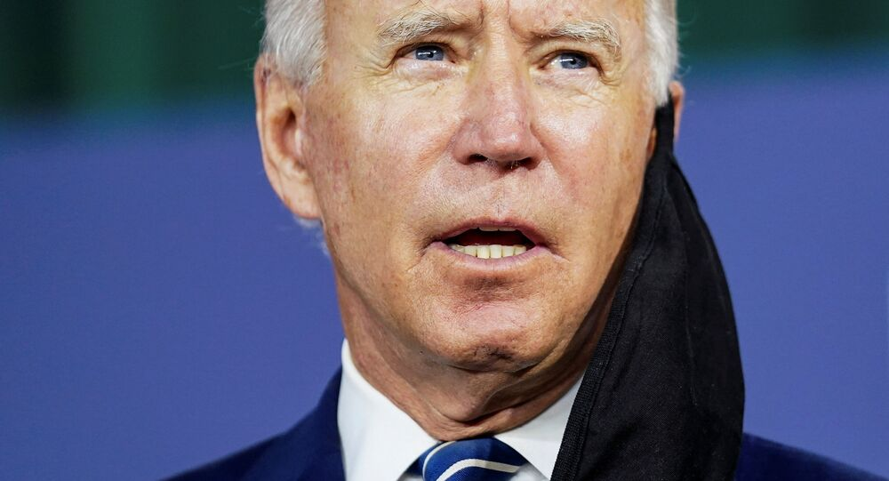 With a face mask hanging off his ear, Democratic U.S. presidential candidate and former Vice President Joe Biden speaks about the third part of his four-part economic recovery plan to revive the coronavirus-battered U.S. economy during a campaign event in New Castle, Delaware, U.S., July 21, 2020.