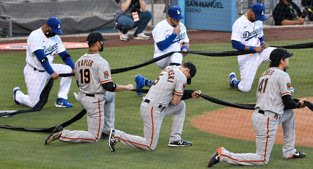Max Muncy and Mookie Betts along with San Francisco Giants manager Gabe Kapler and right fielder Mike Yastrzemski and second baseman Wilmer Flores take a knee during the national anthem before playing an opening day game at Dodger Stadium