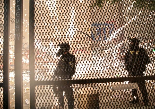 Federal law enforcement officers stand behind a metal fence as demonstrators are approaching during a protest against racial inequality and police violence in Portland, Oregon, U.S., July 25, 2020.
