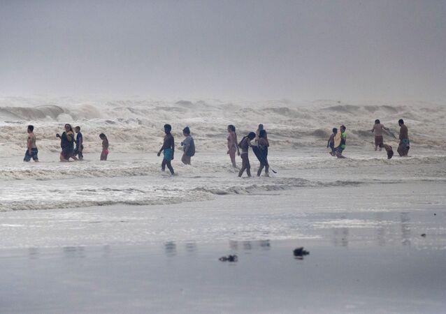 Beach-goers play in high swells from Hurricane Hanna in Galveston, Texas, U.S., July 25, 2020.
