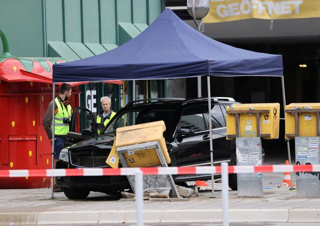 An official works near a car which crashed into a group of seven people at Bahnhof Zoo train station in Berlin
