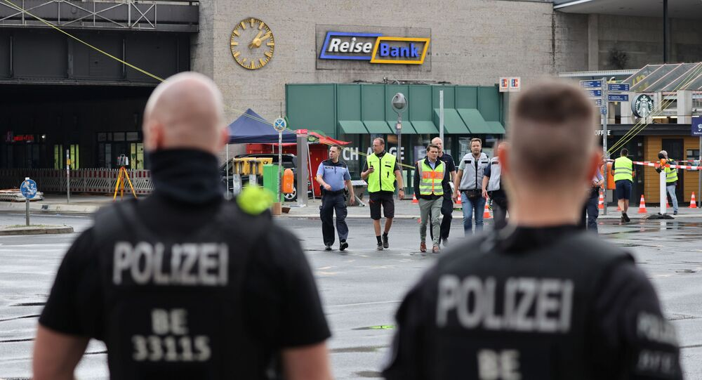 Officials walk past a car which crashed into a group of seven people at Bahnhof Zoo train station in Berlin