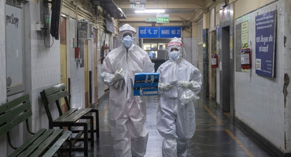 Medical workers wearing personal protective equipment (PPE) walk through a ward for patients suffering from the coronavirus disease