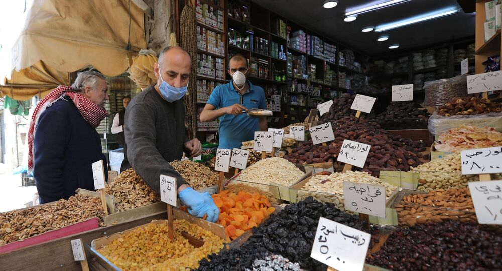 Vendors wearing protective face masks serve customers at a shop, ahead of the Muslim holy month of Ramadan, amid concerns over the coronavirus disease (COVID-19), in Amman, Jordan April 21, 2020.