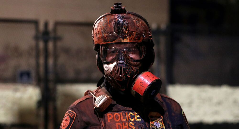 A federal law enforcement officer is covered in red paint during a protest against racial inequality and police violence in Portland, Oregon, U.S., July 26, 2020.