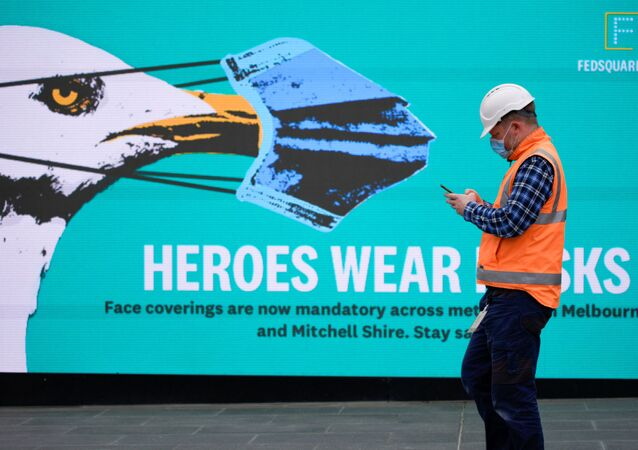 An essential worker wearing a face mask walks past a 'Heroes Wear Masks' sign in Melbourne after it became the first city in Australia to enforce mask-wearing in public as part of efforts to curb a resurgence of the coronavirus disease (COVID-19), July 23, 2020.