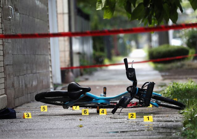 Shell casing markers are seen at the scene where a 37-year-old man was shot dead while riding a bicycle in Chicago at the weekend.