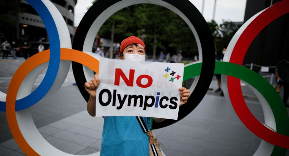 A demonstrator wearing a face mask holds a sign to protest against the Tokyo 2020 Olympic Games taking place next year.