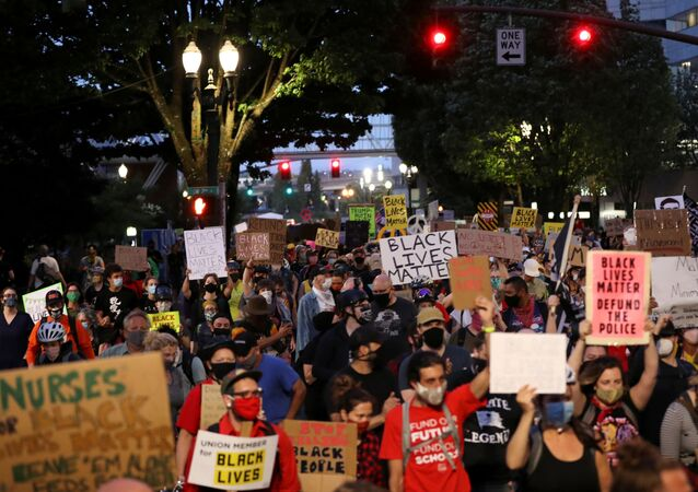 Demonstratrors hold placards as they march against racial inequality in downtown Portland, Oregon, U.S., July 25, 2020.
