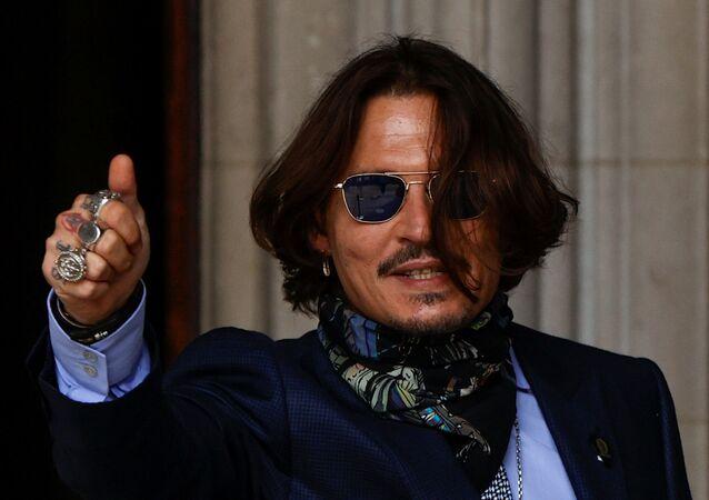 Actor Johnny Depp gestures as he arrives at the High Court in London, Britain July 24, 2020.