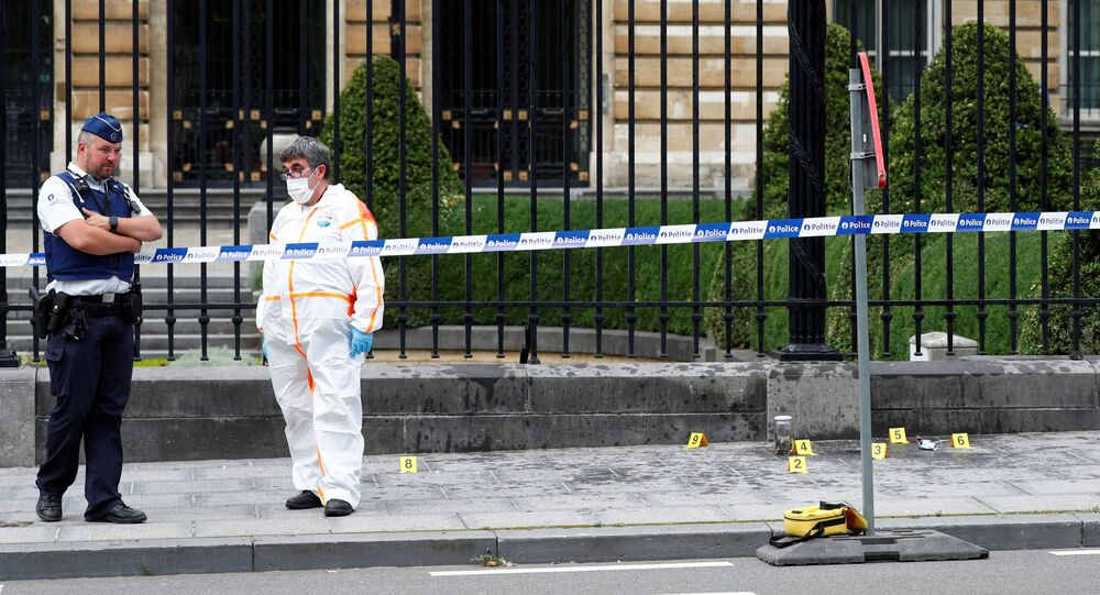 A police officer and a forensic investigator are seen in front of the Belgian Parliament after a suspect threw a Molotov cocktail, according to local media, in Brussels, Belgium July 27, 2020