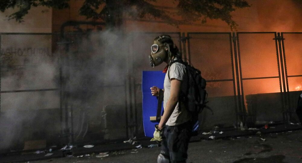 A protester holds a shield and wears a gas mask after federal law enforcement officers fired tear gas outside the Mark O. Hatfield United States Courthouse during a demonstration against the presence of federal law enforcement officers and racial inequality in Portland, Oregon, U.S., July 23, 2020