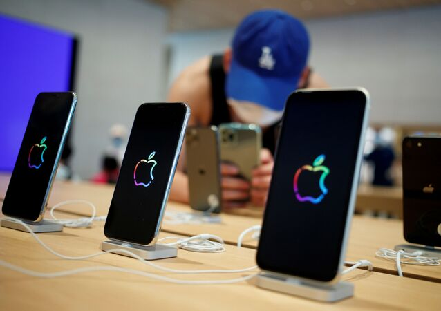 A man takes pictures of iPhones in the new Apple flagship store on its opening day following an outbreak of the coronavirus disease (COVID-19) in Sanlitun in Beijing, China, July 17, 2020