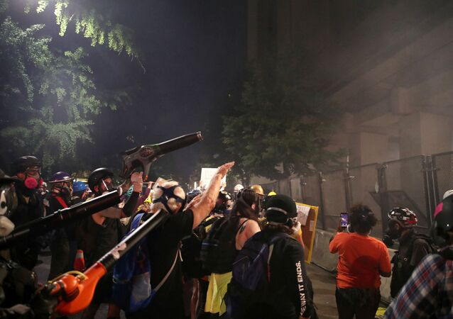 Demonstrators use leaf blowers to clear the tear gas during a protest against racial inequality and police violence in Portland, Oregon, U.S., July 27, 2020