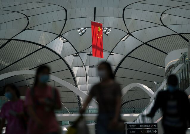 People wearing face masks following the coronavirus disease (COVID-19) outbreak walk under a Chinese flag at Beijing Daxing International Airport in Beijing, China July 24, 2020