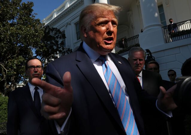 U.S. Treasury Secretary Steven Mnuchin (L) and White House Chief of Staff Mark Meadows stand behind U.S. President Donald Trump as he speaks to the news media before departing for Marine One for travel to Midland, Texas from the South Lawn of the White House in Washington, U.S., July 29, 2020.