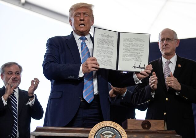 U.S. President Donald Trump is applauded as he displays a presidential permit for energy development that he signed during a tour of the Double Eagle Energy Oil Rig in Midland, Texas, U.S., July 29, 2020.