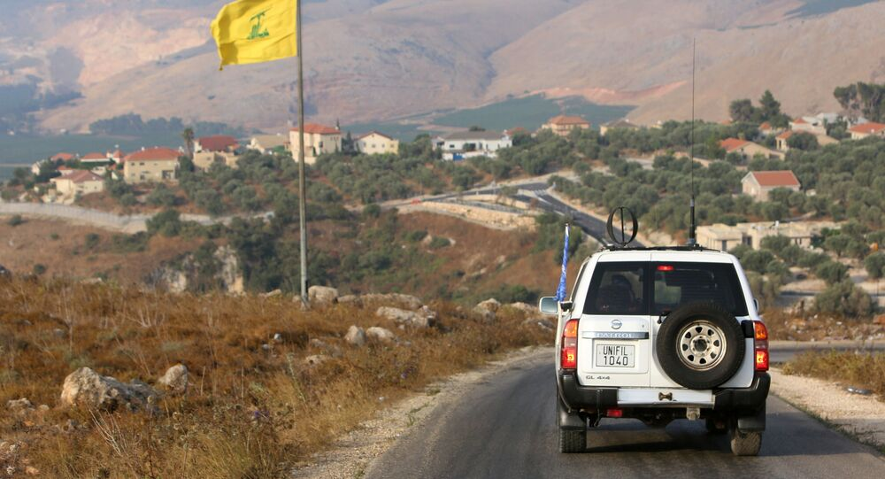 A UN peacekeepers (UNIFIL) vehicle drives past a Hezbollah flag in the southern Lebanese village of Khiam, near the border between Israel and Lebanon, 28 July 2020.