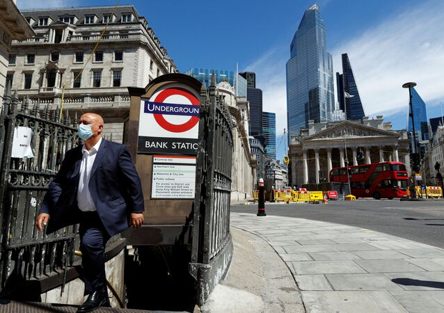 A man wearing a face mask and suit exits Bank underground station, in front of the Bank of England and Royal Exchange Building, amid the coronavirus disease (COVID-19) outbreak, in London, Britain, July 30, 2020.